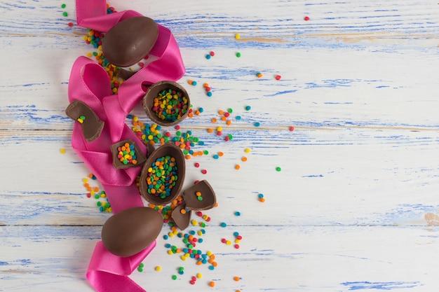 Wielkanocne jajka czekoladowe, różowa taśma, wielobarwne słodycze na starej białej drewnianej powierzchni. wielkanocna koncepcja