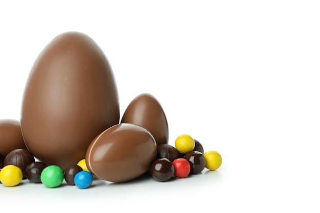 Wielkanocne jajka czekoladowe z cukierkami na białym tle na białej powierzchni