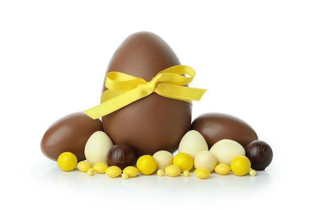 Wielkanocne jajka czekoladowe z cukierkami na białym tle na białej ścianie