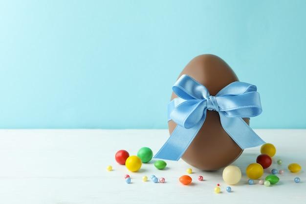 Wielkanocne Jajko Czekoladowe I Cukierki Na Białym Drewnianym Stole Premium Zdjęcia