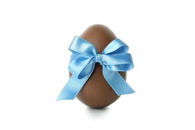 Wielkanocne jajko czekoladowe z kokardą na białym tle na białej powierzchni