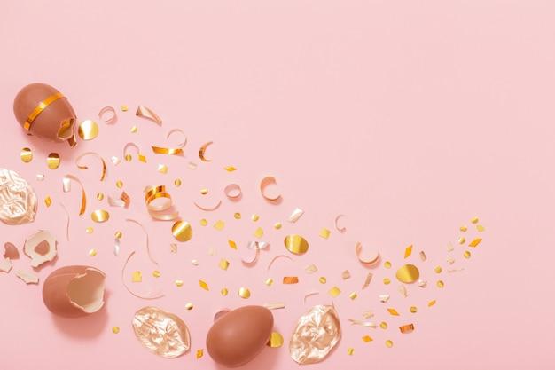 Wielkanocne jajko czekoladowe ze złotym konfetti na różowym tle