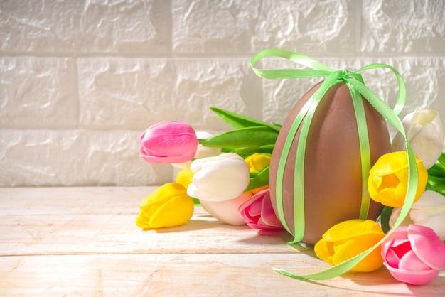 Wielkanocne kartki z życzeniami tło z ogromnym dużym czekoladowym jajkiem, z świąteczną wstążką bukiet kwiatów tulipanów, na oświetlonej słońcem drewnianej klasycznej przestrzeni kopii tła