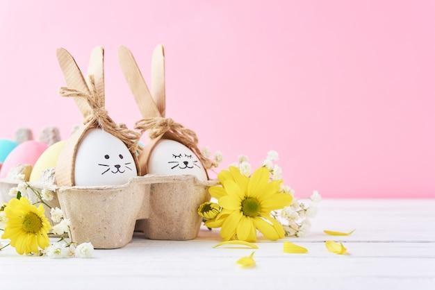 Wielkanocne kolorowe jaja z pomalowanymi twarzami w papierowej tacy z dekoracją na różowym tle