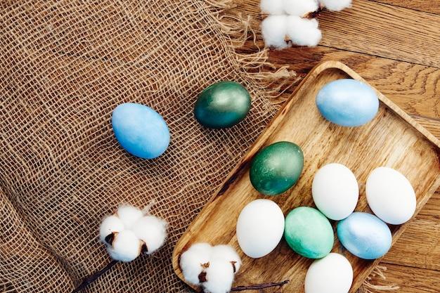 Wielkanocne kolorowe jajka drewniana taca werbena kwiaty widok z góry