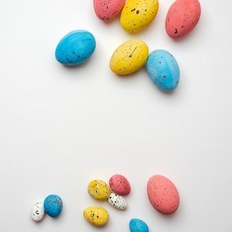 Wielkanocne, kolorowe jajka są chaotycznie ułożone.