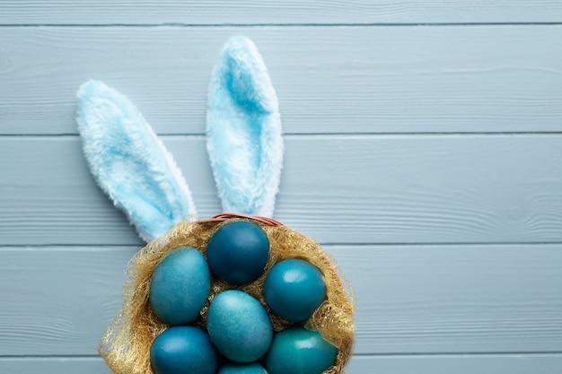 Wielkanocne mieszkanie leżało z niebieskimi jajkami w koszyku i zabawnymi uszami królika na jasnoniebieskim drewnianym tle. skopiuj miejsce