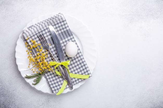 Wielkanocne nakrycie stołu. biały talerz, kwiaty mimozy i sztućce na kamiennym tle