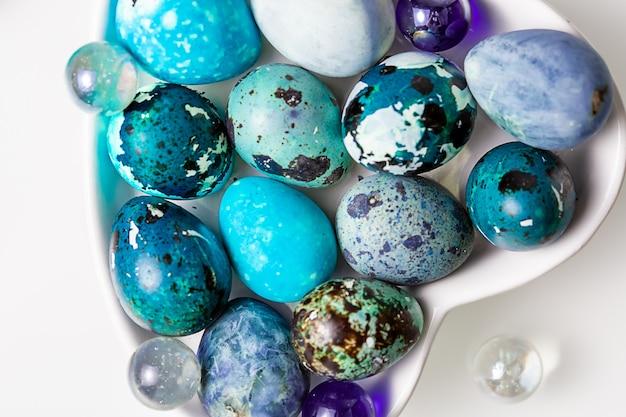 Wielkanocne niebieskie jajka przepiórcze w talerzu w kształcie serca na białym stole.