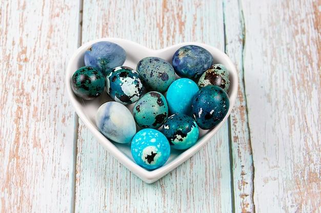 Wielkanocne niebieskie jajka przepiórcze w talerzu w kształcie serca na drewnianym stole.