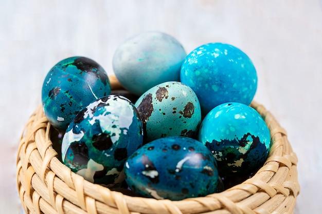 Wielkanocne niebieskie jajka przepiórcze w wiklinowym koszu.
