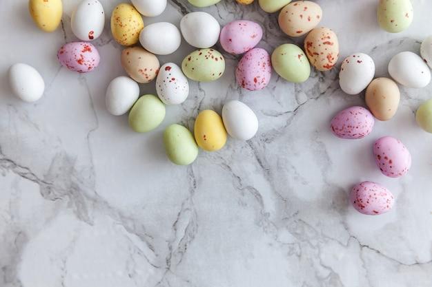 Wielkanocne pastelowe cukierki czekoladowe jajka słodycze na modnym szarym tle marmuru