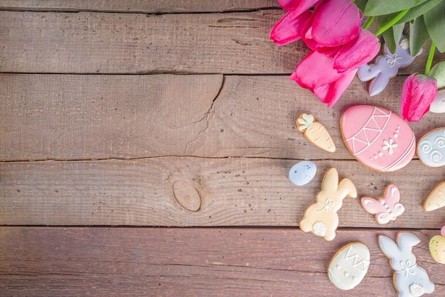 Wielkanocne pierniki, wiosenne kwiaty i jajka na drewnianej ścianie. przytulny dom wielkanocny greeeting koncepcja karty, widok z góry przestrzeni kopii