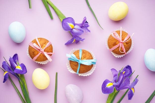 Wielkanocne przysmaki, kolorowe babeczki i kwiaty irysy na różowo