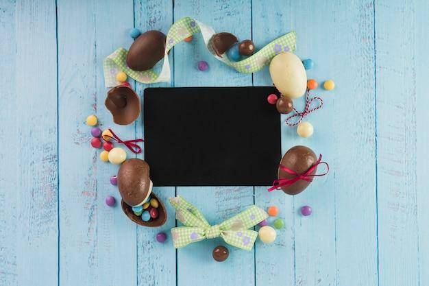 Wielkanocne słodycze i wstążki wokół czarnego papieru