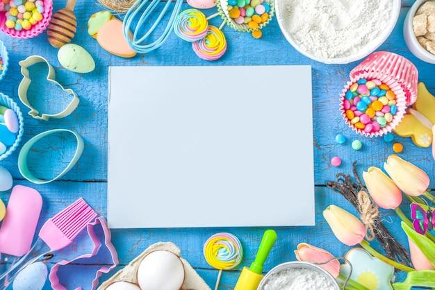 Wielkanocne tło do pieczenia z wałkiem do ciasta, trzepaczką, jajkami, mąką i kolorowe konfetti cukru
