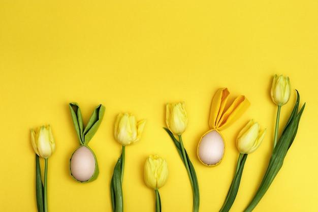 Wielkanocne tło z ozdobnymi drewnianymi jajkami zajączek wielkanocny i jasnożółty naturalny kwiat tullits.