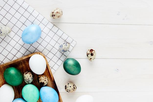 Wielkanocne wakacje kolorowe jajka na drewnianym stole w kratkę tkaniny widok z góry