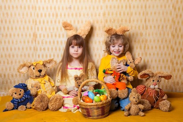 Wielkanocne zdjęcie emocjonalnych dzieci z koszykiem jajek z uszami królika