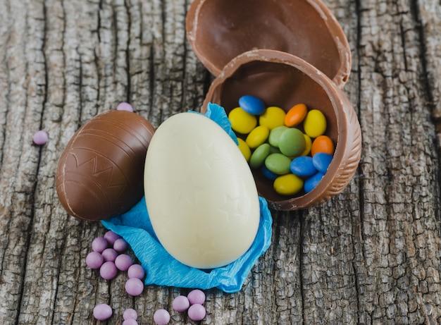 Wielkanocni czekoladowi jajka na nieociosanym drewnianym tle. widok z góry.