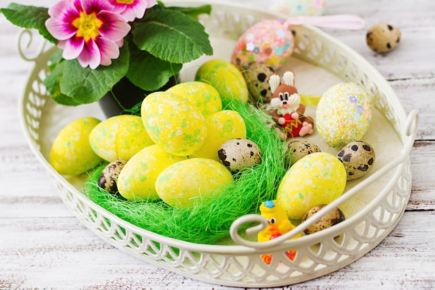 Wielkanocni jajka i kwiaty na lekkim drewnianym stole