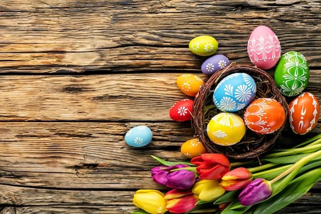 Wielkanocni jajka i tulipany na drewnianych deskach