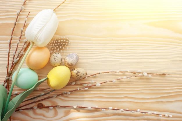Wielkanocni jajka i tulipany na drewnianym stole. poranne światło.
