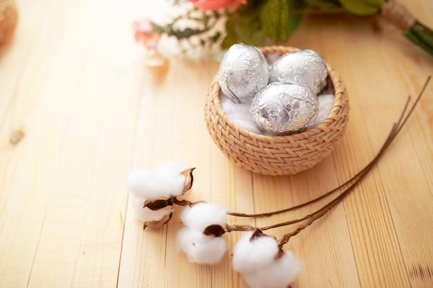 Wielkanocni jajka na białym drewnianym stole. kwiaty i cukierki wokół.