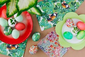 Wielkanocni jajka na talerzach blisko pieluch z tropikalnymi farbami