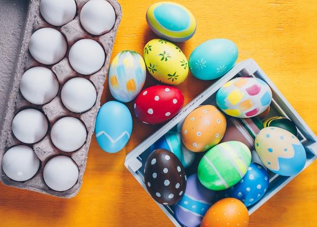Wielkanocni jajka w drewnianym pudełku i jajecznego kartonu odgórnym widoku na żółtym drewnianym tle