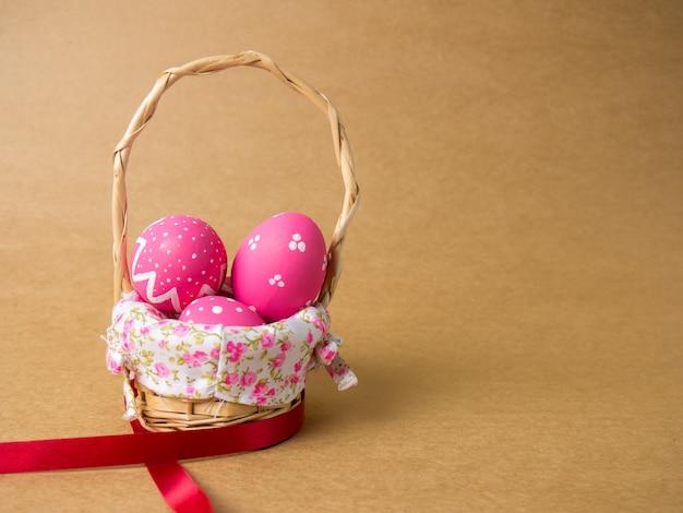 Wielkanocni jajka w drewnie wyplatają kosz na brown tle