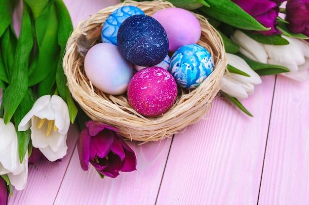Wielkanocni jajka w gniazdeczku i tulipanach na drewnianych deskach