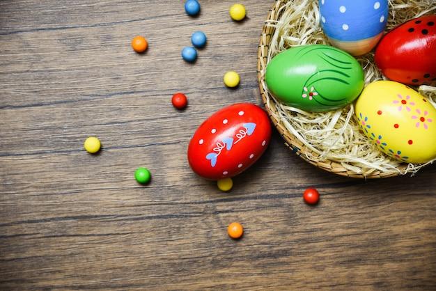 Wielkanocni jajka w gniazdowym koszu na drewnianym tle
