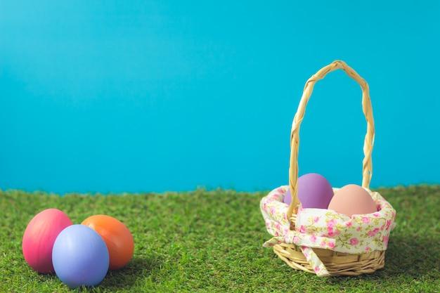 Wielkanocni jajka w koszu wyplatają drewno na zielonej trawie.