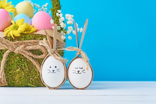 Wielkanocni jajka z malować twarzami i dekoracyjnym koszem na błękitnym bacground