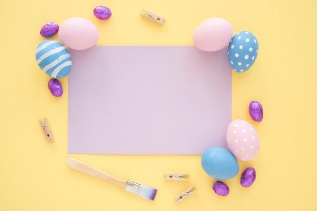Wielkanocni jajka z pustym purpura papierem na koloru żółtego stole