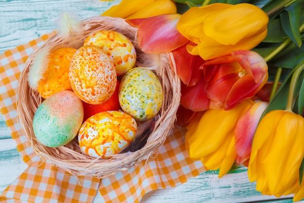 Wielkanocni jajka z tulipanami na błękitny drewnianym