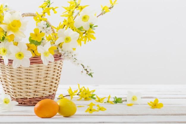 Wielkanocni jajka z wiosną kwitną na białym drewnianym stole
