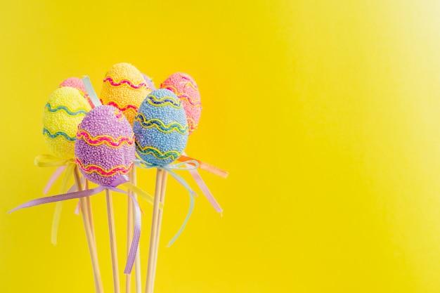 Wielkanocni kolorowi dekorujący jajka stoją na kijach. minimalna koncepcja wielkanocy. szczęśliwa kartka wielkanocna