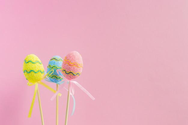 Wielkanocni kolorowi dekorujący jajka stoją na kijach na pastelowych różowych copyspace. minimalna koncepcja wielkanocy. szczęśliwa kartka wielkanocna