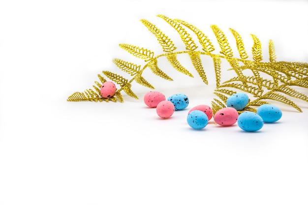 Wielkanocni kolorowi jajka i złocista paproć rozgałęziają się na białym tle