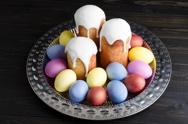 Wielkanocni torty i jajka na ciemnym, nieociosanym, drewnianym tle