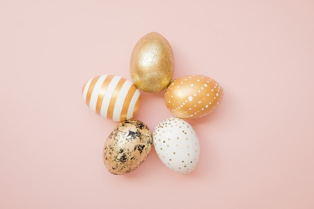 Wielkanocni złoci dekorujący jajka na pastelowych menchii tle
