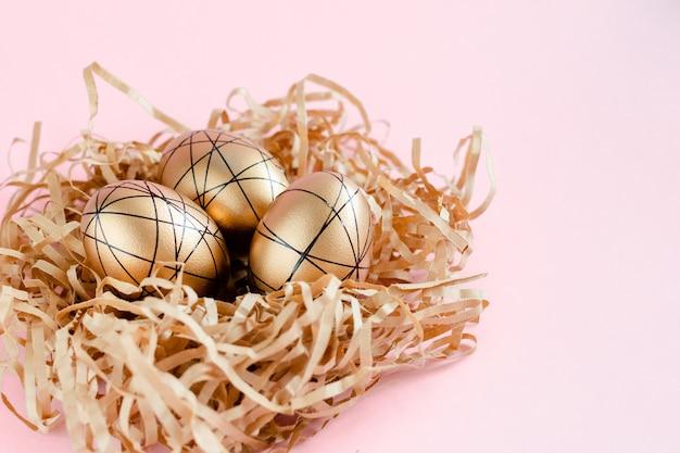 Wielkanocni złoci dekorujący jajka w gniazdeczku na białym tle. minimalna koncepcja wielkanoc kopia przestrzeń dla tekstu. widok z góry w poziomie, płaski.