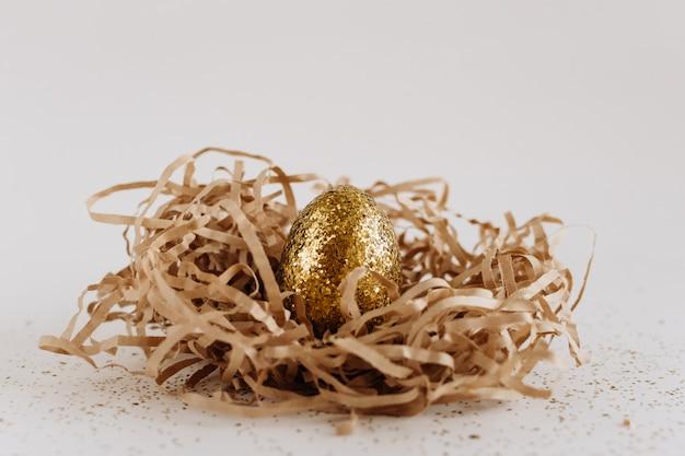 Wielkanocni złoci dekorujący jajka w gniazdeczku na białym tle. minimalna koncepcja wielkanoc kopia przestrzeń dla tekstu.