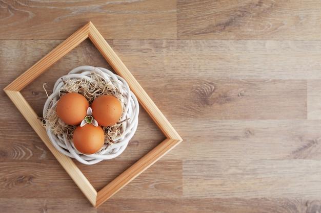 Wielkanocnie dekorująca rama z easter jajkami i kwiatami na drewnianym wieśniaka stole, wakacyjny tło dla twój dekoraci. wiosny i wielkanocy wakacyjny pojęcie z kopii przestrzenią.