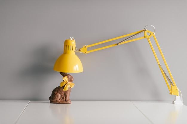 Wielkanocny czekoladowy królik z żółtym bowtie siedzi na stole z lampą