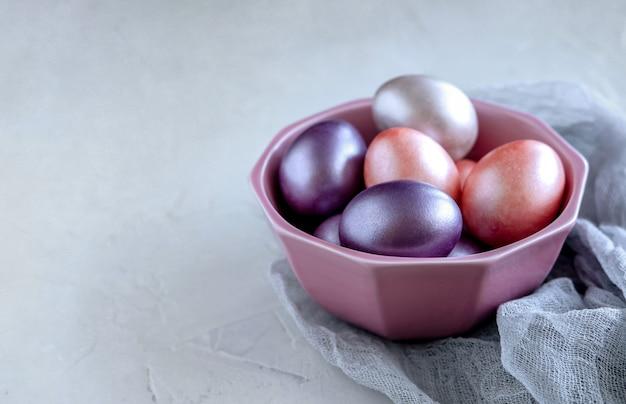 Wielkanocny kartka z pozdrowieniami z kolorowymi easter jajkami na szarym tle.