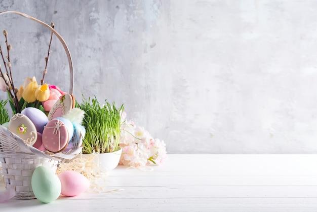 Wielkanocny kartka z pozdrowieniami z oszklonymi ciastkami i kolorowymi easter jajkami w koszu. z miejscem na kopię