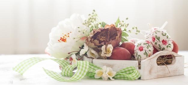 Wielkanocny kosz i czerwoni jajka z kwiatami